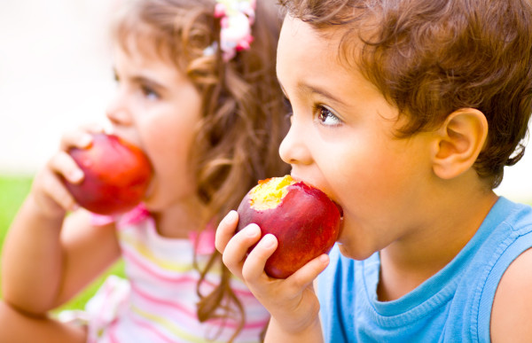 Photo of two happy children eating apples, brother and sister having picnic outdoors, cheerful kids biting red ripe peach, adorable infant holding fresh fruits in hands, healthy nutrition concept
